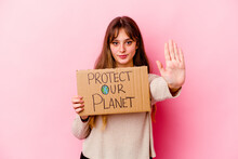 Young Caucasian Woman Holding A Protect Our Planet Placard Isolated Standing With Outstretched Hand Showing Stop Sign, Preventing You.