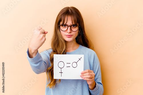 Young caucasian woman holding a equality gender placard isolated showing fist to camera, aggressive facial expression Poster Mural XXL