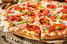 Pepperoni Pizza With Pizza Sauce, Mozzarella Cheese And Pepperoni. Pizza On Wooden Board On Wood Table With Ingredients.
