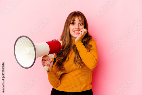 Young caucasian woman holding a megaphone isolated biting fingernails, nervous and very anxious Wallpaper Mural