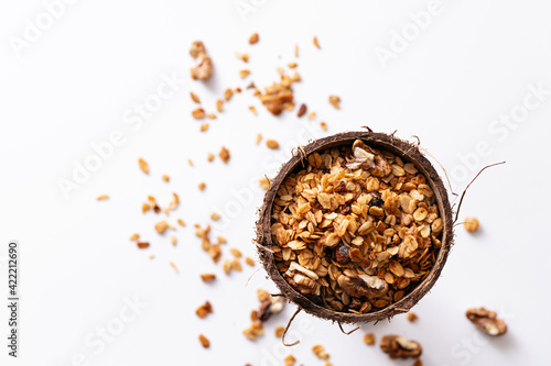 Fototapeta homemade granola in a coconut shell on a white background, top view obraz