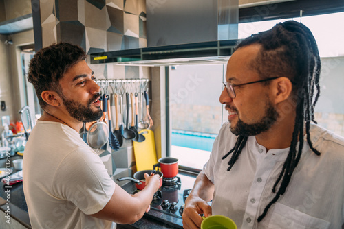 Tablou Canvas gay young latinx couple together in the kitchen, having a great time