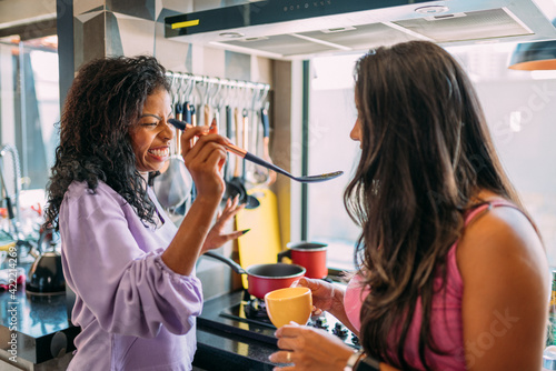 Fotografie, Tablou lesbian latinx couple together in the kitchen, having a great time