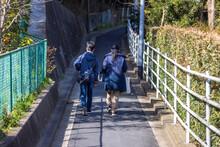 細い坂道を並んで歩く母親と息子