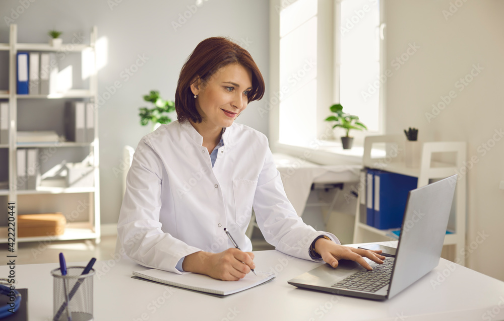 Fototapeta Female doctor writes notes while watching an online medical webinar or training seminar while sitting with a laptop in the workplace. Positive doctor does his best to provide quality medical care