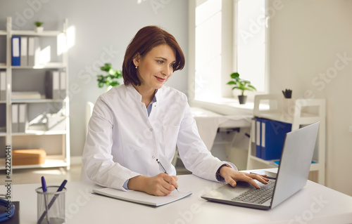 Female doctor writes notes while watching an online medical webinar or training seminar while sitting with a laptop in the workplace Tapéta, Fotótapéta