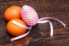 Three Chicken Eggs On A Wooden Surface One Egg Is Decorated With An Easter Ribbon