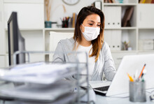 Woman In Protective Mask Sitting At Workplace With Computer In Her Office