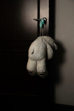 A White Teddy Bear Hangs On The Door Handle. Hanging On A Covid-19 Mask. An Abandoned Toy For The Night.