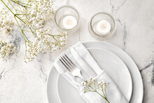 Beautiful Table Setting With Burning Candles And Floral Decor On Light Background