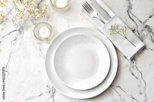 Fotografia Beautiful table setting with burning candles and floral decor on light backgroun