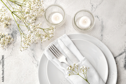 Papel de parede Beautiful table setting with burning candles and floral decor on light backgroun