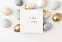 Golden And Gray Eggs With A Paper White Card On A White Background. Minimal Easter Concept.