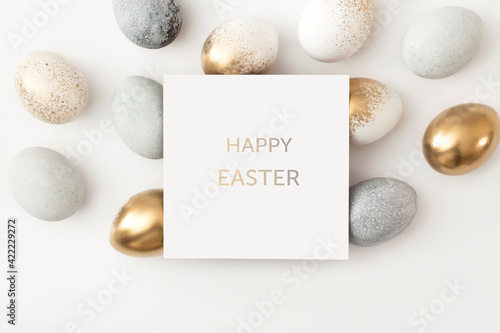 Obraz Golden and gray eggs with a paper white card on a white background. Minimal easter concept. - fototapety do salonu