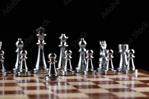 Steel chess figures standing on wooden chessboard Fotobehang