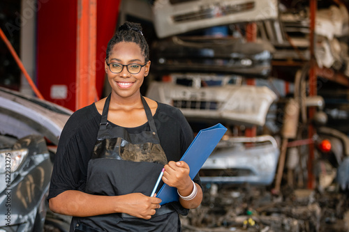 Canvas-taulu African american worker woman wear spectacles crossed arms holding clipboard standing in factory auto parts