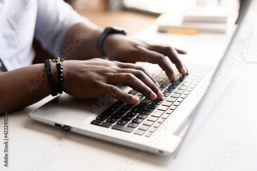 Obraz Close up image of male hands with accessories typing text on the laptop keyboard, working, responding to client e-mail, buying ordering items online. Electronics and modern wireless technology concept - fototapety do salonu