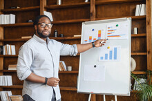 African American Male School Teacher In Glasses Pointing On The Whiteboard With Bar Charts, Explaining Numbers, Streaming Lesson Online And Looking At Webcam, Teaching In A Virtual Online Classroom
