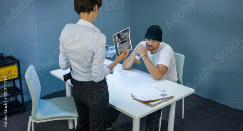 Fotografie, Obraz Woman detective shows pictures of suspected criminals and robber