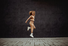 Full Length Of Cheerful Hip Hop Girl In Tracksuit Jumping In Place.