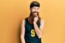 Redhead Man With Long Beard Wearing Basketball Uniform Looking Confident At The Camera With Smile With Crossed Arms And Hand Raised On Chin. Thinking Positive.
