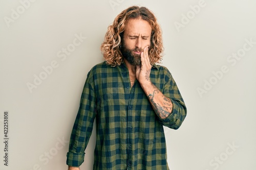Photographie Handsome man with beard and long hair wearing casual clothes touching mouth with hand with painful expression because of toothache or dental illness on teeth