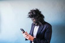 Man With Gorilla Mask Using Smart Phone