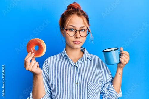 Fototapeta Young redhead woman eating breakfast holding chocolate donut and coffee relaxed with serious expression on face. simple and natural looking at the camera. obraz