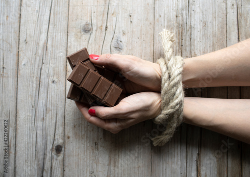 Hands of young woman with red fingernails are tied and lying on light wood backg Wallpaper Mural