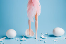 Girl Doll With Elegant Pink Feather Dress Legs Among Cracked White Eggs On Pastel Blue Background. Creative Minimal Easter Or Fashion Concept.