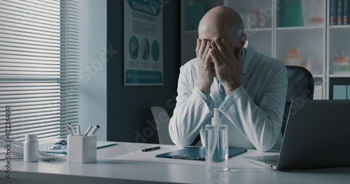 Obraz Stressed exhausted doctor with head in hands - fototapety do salonu