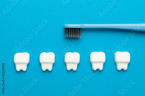 Oral hygiene. Teeth and toothbrush on a blue background.