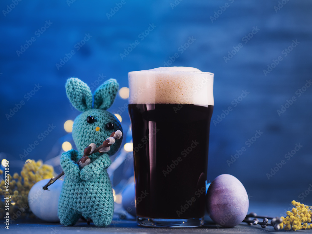 Fototapeta Creative greeting from a bunny for the Easter holiday. A glass of dark beer, Easter colored eggs on a blue background - obraz na płótnie