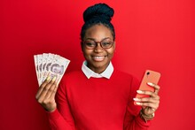 Young African American Woman Using Smartphone Holding Mexican Peso Banknotes Smiling With A Happy And Cool Smile On Face. Showing Teeth.