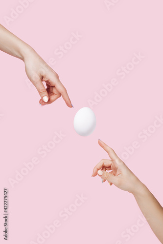 Fotografia Two hands touching flying egg on pastel pink background