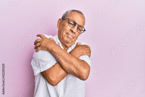 Photo Handsome mature senior man wearing casual shirt and glasses hugging oneself happy and positive, smiling confident