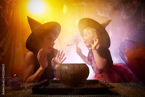 Beautiful brunette mother and cute little daughter looking as witches in special dresses and hats conjuring with a pot in room decorated for Halloween Fototapet