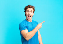 Young Sport Boy Looking Excited And Surprised Pointing To The Side And Upwards To Copy Space