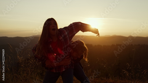 Man holding woman on hands in mountains. Emotional guy and girl having fun