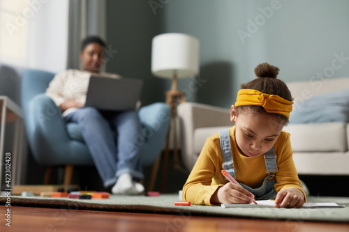 Fototapeta Front view portrait of cute African-American girl drawing while lying on floor in home interior with mother working in background, copy space obraz na płótnie