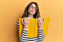 Young Caucasian Woman Reading A Book Wearing Glasses Looking At The Camera Blowing A Kiss Being Lovely And Sexy. Love Expression.