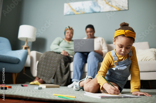 Fototapeta Front view portrait of cute African-American girl drawing while sitting on floor in home interior with family in background, copy space obraz na płótnie