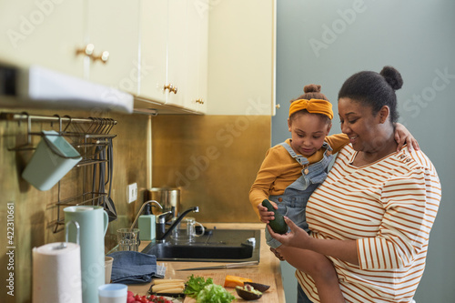 Obraz Waist up portrait of happy African-American mother holding daughter while cooking together in kitchen interior, copy space - fototapety do salonu