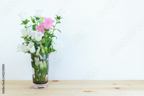spring bouquet of white and pink bell flowers over purple wooden background