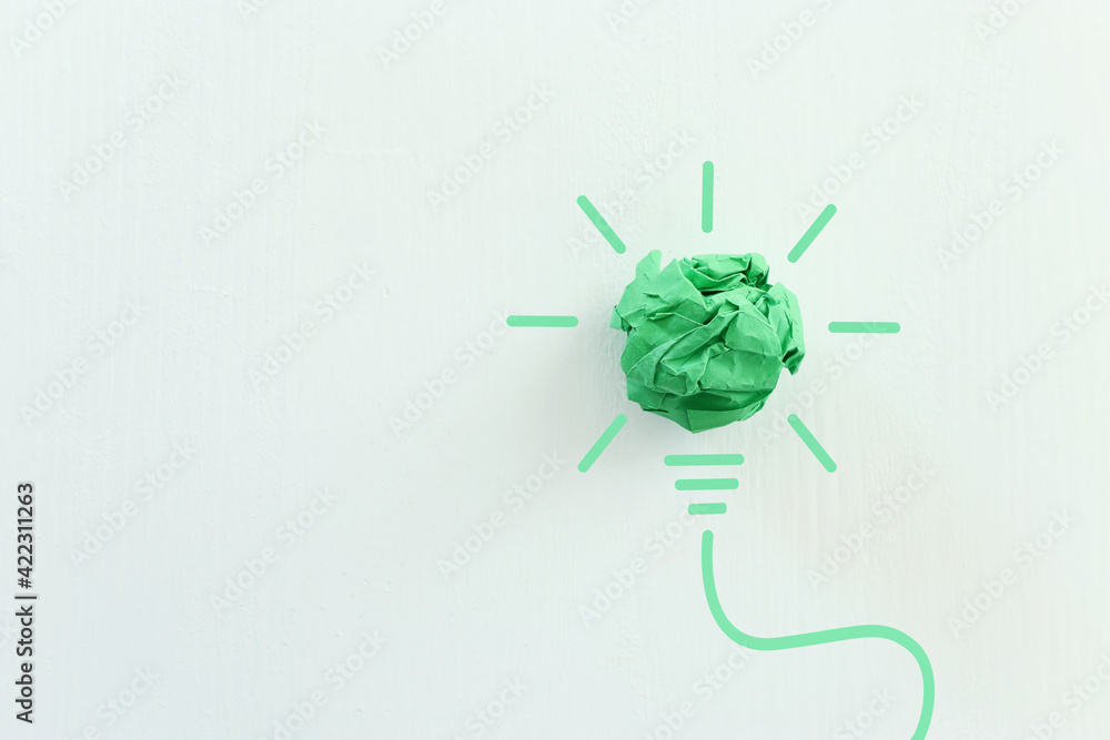 Fototapeta Concept image if green crumpled paper lightbulb, symbol of scr, innovation and eco friendly business