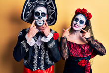 Young Couple Wearing Mexican Day Of The Dead Costume Over Yellow Smiling With Open Mouth, Fingers Pointing And Forcing Cheerful Smile