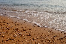 Small Waves On The Sea Beach At The Lately Evening For Backdrop Background With Red Sand
