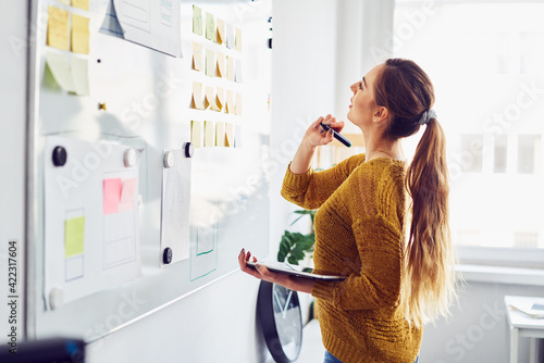 Young businesswoman planning in office using whiteboard and digital tablet