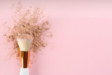 Makeup Brush And Scattered Face Powder On Pink Background, Top View. Space For Text
