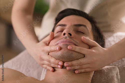 Man receiving facial massage in beauty salon, closeup